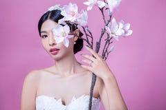 Stående av den säkra bruden som rymmer konstgjorda blommor mot rosa bakgrund Arkivfoton