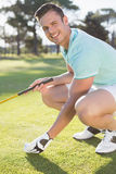 Stående av den säkra golfaremannen som förlägger golfboll på utslagsplats royaltyfri bild