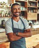 Stående av den säkra manliga baristaen på räknaren i kafé royaltyfria bilder