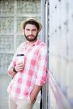 Stående av den säkra mannen som rymmer den disponibla koppen, medan luta på väggen arkivfoto