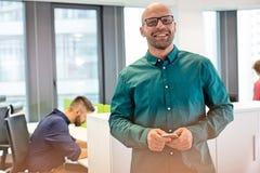 Stående av den säkra mitt- vuxna affärsmannen som ler med kollegan i bakgrund på kontoret Royaltyfria Foton