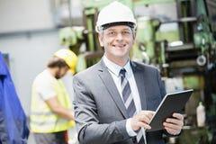 Stående av den säkra mogna affärsmannen som använder den digitala minnestavlan med arbetaren i bakgrund på fabriken royaltyfri bild