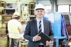Stående av den säkra mogna affärsmannen som rymmer den digitala minnestavlan med arbetaren i bakgrund på fabriken Royaltyfri Fotografi