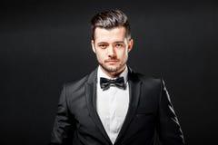 Stående av den säkra stiliga mannen i svart dräkt med bowtie royaltyfri fotografi