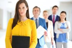 Stående av den säkra unga affärskvinnan med laget i bakgrund på kontoret Royaltyfri Foto