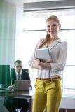 Stående av den säkra unga affärskvinnan som rymmer den digitala minnestavlan med affärsmannen i bakgrund på kontoret Arkivbild