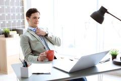 Stående av den säkra unga affärsmannen som dricker kaffe arkivfoto