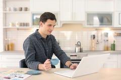 Stående av den säkra unga mannen med bärbara datorn och koppen royaltyfri bild