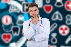 Stående av den säkra unga medicinska doktorn på bakgrund med medicinska symboler Royaltyfri Foto