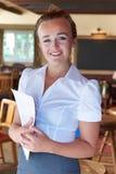 Stående av den servitrisHolding Menu In restaurangen Royaltyfri Foto
