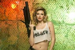 stående av den sexiga blondinen med vapnet Royaltyfria Bilder