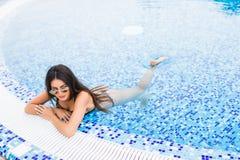 Stående av den sexiga gladlynta kvinnan som kopplar av på den lyxiga poolsiden Flicka på pölen för loppbrunnsortsemesterort för s Arkivbilder