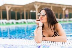 Stående av den sexiga gladlynta kvinnan som kopplar av på den lyxiga poolsiden Flicka på pölen för loppbrunnsortsemesterort för s Arkivfoton