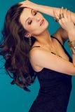 Stående av den sexiga trendiga kvinnan med långt lockigt hår studio fotografering för bildbyråer