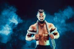 Stående av den shirtless kroppsbyggaren Muskulös man som poserar i studio Royaltyfri Fotografi