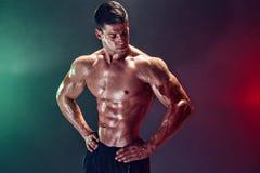 Stående av den shirtless kroppsbyggaren Muskulös man som poserar i studio Arkivbild