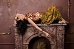 Stående av den sinnliga unga kvinnan för skönhet i orientalisk stil i lyxigt rum Arkivfoton