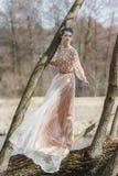 Stående av den sinnliga unga kvinnan som bär den eleganta klänningen i en barrskog Royaltyfria Bilder