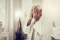 Stående av den sjuka åldras vit-haired manliga gömma i handflatan framsidan på sovrummet royaltyfri foto