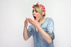 Stående av den sjuka unga kvinnan i tillfällig blå grov bomullstvillskjorta med makeup och rött huvudbindelanseende som rymmer si arkivbilder