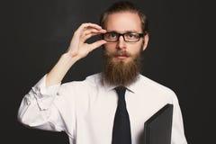 Stående av den skäggiga affärsmannen för allvarlig hipster med dokument Framstickande i exponeringsglas som poserar i affär fotografering för bildbyråer