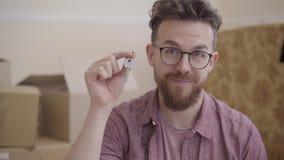 Stående av den skäggiga mannen i exponeringsglas som visar tangent från huset som in camera ser med brett leende Den positiva man stock video