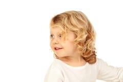 Stående av den skämtsamma lilla ungen med långt blont hår som tillbaka ser Arkivbild