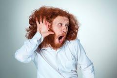Stående av den skrikiga unga mannen med långt rött hår och chockat ansiktsuttryck på grå bakgrund royaltyfria bilder
