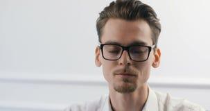 Stående av den smarta tillfälliga idérika unga mannen i moderiktigt exponeringsglasarbete på det moderna kontoret stock video