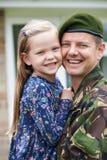Stående av den soldatOn Leave Hugging dottern arkivfoton