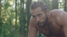 Stående av den starka våta mannen i skogen långsamt lager videofilmer