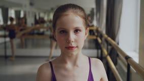 Stående av den startande balettdansören för ung flicka med sminket som ser kameran och ler under balettgrupp i rymligt stock video
