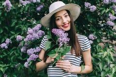 Stående av den stilfulla flickahipsteren på gatan bland en blomstra lila Arkivfoto
