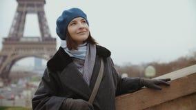 Stående av den stilfulla kvinnan i blått basker och vinterlag nära Eiffeltorn arkivfilmer
