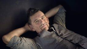 Stående av den stilfulla mannen i hans 50-tal som ligger på soffan Arkivfoto