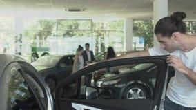 Stående av den stilfulla mannen nära den moderna automatiskn i bilåterförsäljare stock video