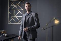 Stående av den stilfulla stiliga affärsmannen i lyxig lägenhet Affärsman i mörk inre man i trendig affär royaltyfri fotografi