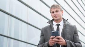 Stående av den stiliga affärsmannen som använder smartphonen och att dricka fotografering för bildbyråer