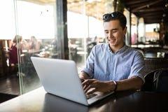 Stående av den stiliga asiatiska le mannen som använder bärbara datorn i kafét Frilans- arbete arkivbilder