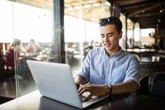 Stående av den stiliga asiatiska le mannen som använder bärbara datorn i kafét Frilans- arbete Arkivbild