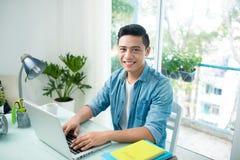 Stående av den stiliga asiatiska unga affärsmannen som arbetar på bärbara datorn Arkivbild