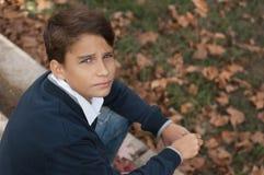 Stående av den stiliga, eftertänksamma och allvarliga tonåriga pojken utomhus grabb arkivfoto
