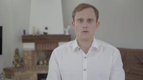 Stående av den stiliga emotionella blonda mannen med att förbluffa gråa ögon i vit t-skjorta talande se in i kameran i arkivfilmer