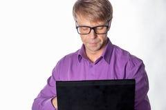 Stående av den stiliga grabben i tillfälliga skjorta och exponeringsglas genom att använda bärbar datordatoren Arbete för upptage royaltyfri foto