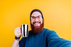 Stående av den stiliga hipstermannen med skägget i hatt som ler och rymmer koppen kaffe eller te arkivbild