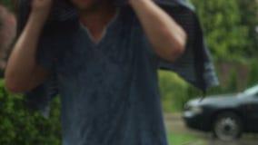 Stående av den stiliga mannen i den blåa skjortan som döljer hans huvud från regnet under omslaget lager videofilmer