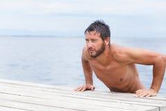 Stående av den stiliga mannen med ingen skjorta på havet Royaltyfri Bild