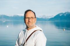 Stående av den stiliga mannen som beundrar den härliga sjön med berg royaltyfria bilder
