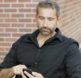 Stående av den stiliga mannen som smsar på hans telefon Royaltyfria Bilder