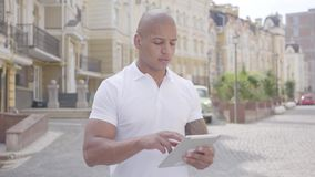 Stående av den stiliga säkra skalliga mitt - östlig man som framme skriver på minnestavlaanseendet på gatan av gammalt stock video